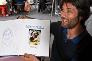 Aré, auteur de BD sourit pendant une dédicace